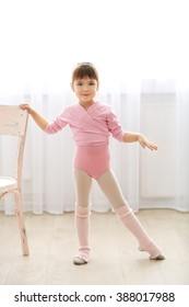 Little cute girl in pink leotard making new ballet movement near chair at dance studio