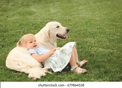 Little cute girl playing with big golden retriever, lying on it in the garden at summer day
