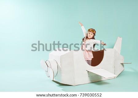 Little Cute Girl Playing Cardboard Airplane Stock Photo