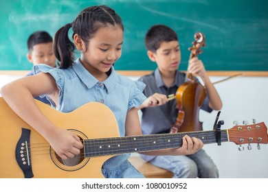Little cute girl playing guitar and smiling in the music class room.