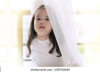 Little cute girl playing hide and seek with her parent. Lovely kid get cheerful and fun while out from behind the sheer curtain by big window with mischievous smile.