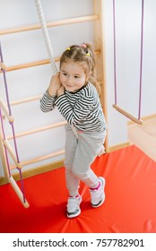 Little cute girl playing on wall climbing bar and have fun. Doing excercises at home on monkey bar.