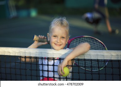 little cute girl playing tennis outside at the tennis court