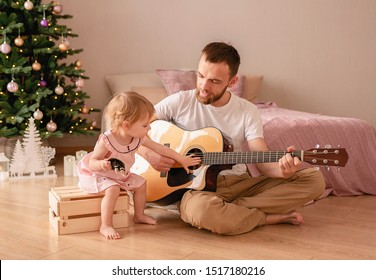 Little cute girl plays the guitar with her dad having fun Christmas holidays. A thirty-year-old bearded man enjoys the time spent with his daughter and learns New Year songs with her. Sunday dad