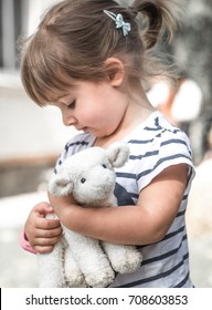little cute girl plays with a toy sheep ,the concept of childhood and children