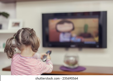 little cute girl pointing remote to control television at home
