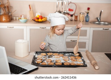 Little cute girl preparing cookies. Kitchen interior with laptop on the table. Concept for young kitchen hands