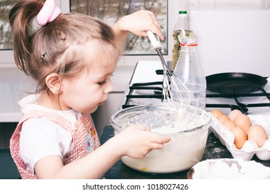 A little cute girl preparing the dough in the kitchen at home, happy family concept