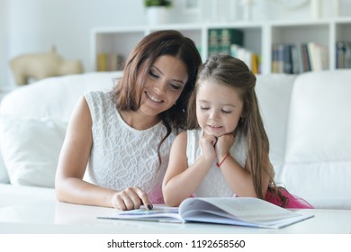little cute girl reading book with mother at the table