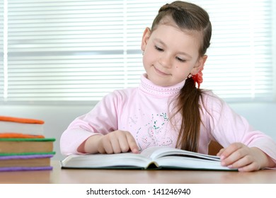 little cute girl reading a book at a table at home