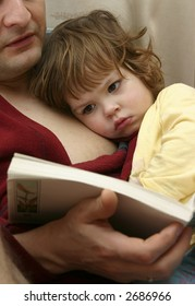 little cute girl reading a book with her daddy