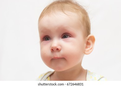 Little cute little girl with red eyes and a tear on her cheek on a white isolated background. Symptoms of the disease