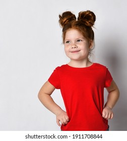 Little cute girl with red hair and freckles holds her hands at her waist and looks to the side. A child in a red T-shirt poses against a gray wall in the studio. Place for text.