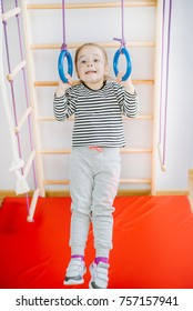 Little cute girl riding a sport rings on the wall bars. The concept of a healthy lifestyle from a young age. Children sport. Young girl have fun in gym.