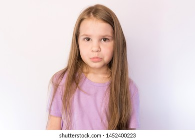 Little cute girl with a sad expression on her face, on a light background