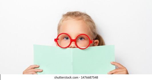 Little cute girl schoolgirl in red glasses holds a green notebook in front of her, peering out from behind him. Back to school