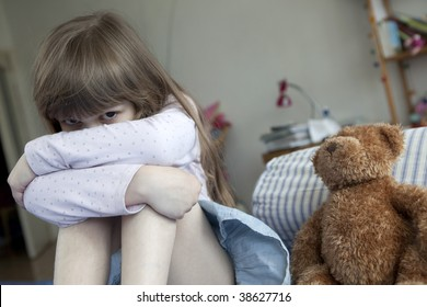 little cute girl seven years old  sitting on bed and crying