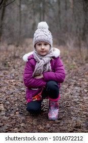 Little cute girl is sitting on the path in the autumn forest