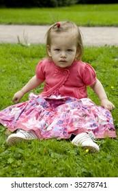 little cute girl sitting on grass