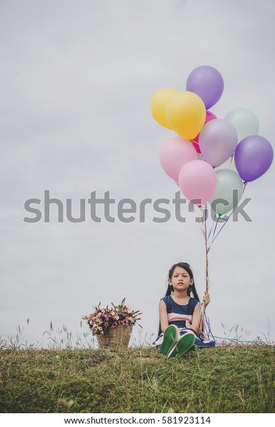 Little cute girl sitting on long green grass outside. Girl holding colorful balloons in hand.