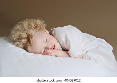 Little cute girl sleeping on a pillow. Sweet dream.