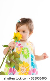 Little cute girl smelling a yellow rose, romantic gift