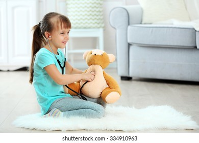 Little cute girl with stethoscope and teddy bear sitting on carpet, on home interior background