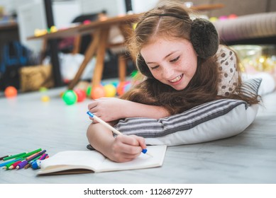 little cute girl studying and writing on notebook at home, education concept