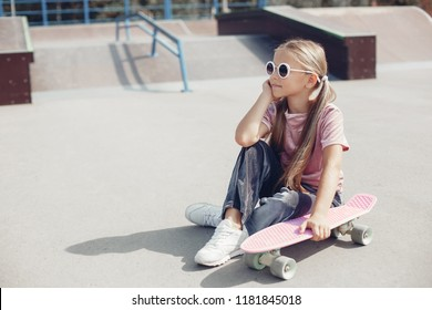 little cute girl with sunglasses and cap sitting on a skateboard. photo of cute preteen girl with skateboard outdoors