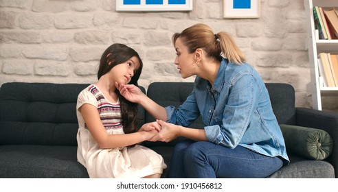 Little cute girl talking to her mother sitting on sofa at home. Loving happy mother, sad cute kid comforting her daughter, making her laugh. Lifestyle at home.