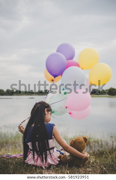 Little cute girl with teddy bear sitting on long green grass outside. Girl holding colorful balloons in hand.