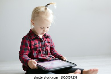 Little cute girl watching a cartoon on the tablet.