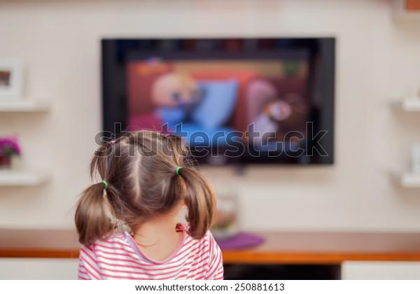 kleines süßes Mädchen, das Fernsehen guckt