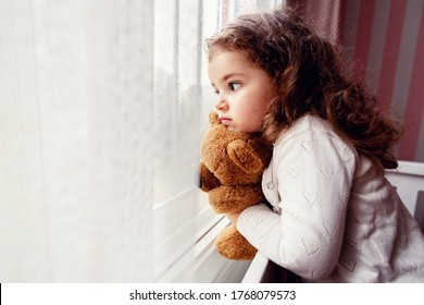 Little cute girl is watching from window to the rain with sadness get bored.