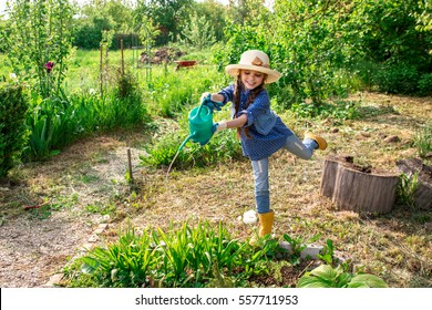 Little cute girl watering trees and flowers in the family garden at a summer day. Kid helping at the farm.