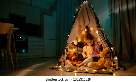 A little cute girl wearing pyjamas sitting on a floor barefoot in a self-made hut made of a plaid, playing games on her tablet, smiling and having teddybears and garlands with her around in a bedroom