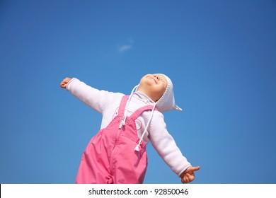 Little cute girl in white cap enjoying on blue sky background