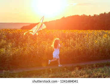 little cute girl in a white dress flying a striped kite in a meadow at sunset