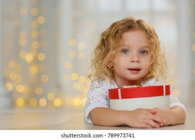 Little cute girl in white dress with a christmas present