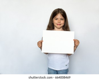 Little cute girl with white sheet of paper in the hands isolated over white background