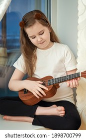 Little cute girl in white t-shirt and black leggings sitting inside of home and playing ukulele. Hobbies and leisure activities during quarantine.