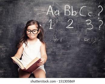 little cute girls looking for answers in front of blackboard