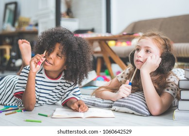little cute girls studying and Writing or drawing something book at home, education concept