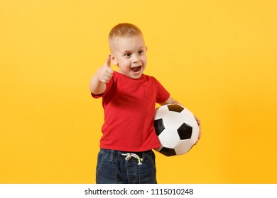 Little cute kid baby boy 3-4 years old, football fan in red t-shirt holding in hand soccer ball isolated on yellow background. Kids sport family leisure lifestyle concept. Copy space advertisement