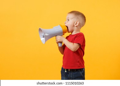 Little cute kid baby boy 3-4 years old in red t-shirt holding in hand and speaking in electronic gray megaphone isolated on yellow background. Kids childhood lifestyle concept. Copy space