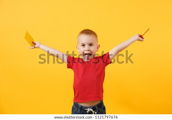Little cute kid baby boy in red t-shirt holding in hand yellow and red soccer referee cards for retire from field isolated on yellow background. Kids family leisure lifestyle concept. Copy space