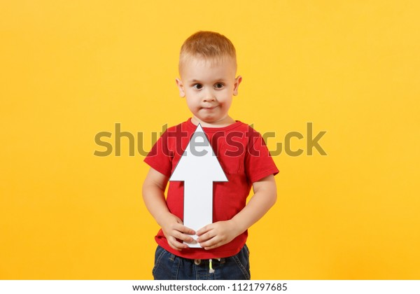 Little cute kid baby boy 3-4 years old in red t-shirt holding in hand up arrow isolated on yellow background. Kids childhood lifestyle concept. Appreciation of exchange rates. Copy space