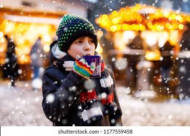 Petit mignon garçon buvant des enfants chauds punch ou chocolat sur le marché de Noël allemand. Joyeux enfant sur le marché familial traditionnel en Allemagne, riant garçon en vêtements d'hiver colorés
