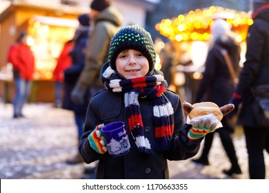 Little cute kid boy eating German sausage and drinking hot children punch on Christmas market. Happy child on traditional family market in Germany, Munich. Laughing boy in colorful winter clothes