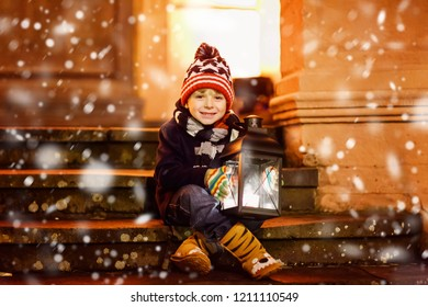 Little cute kid boy with with a light lantern on stairs near church. Happy child on Christmas market in Germany. Kid waiting on parents on cold winter day
